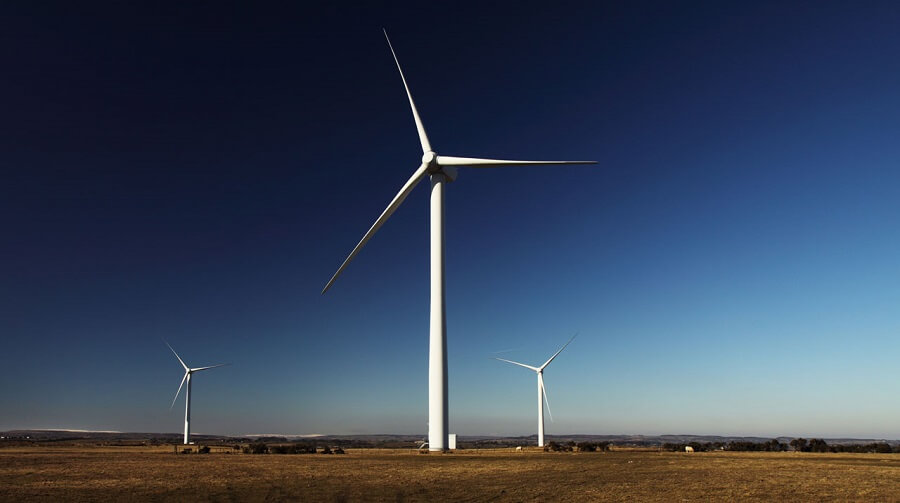 wind turbines in a field with a blue sky background