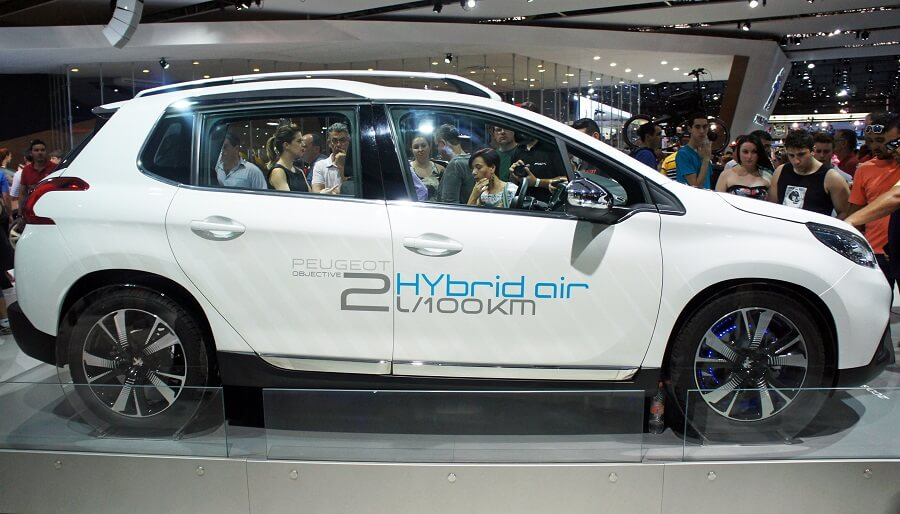white peugeot hybrid car surrounded by people