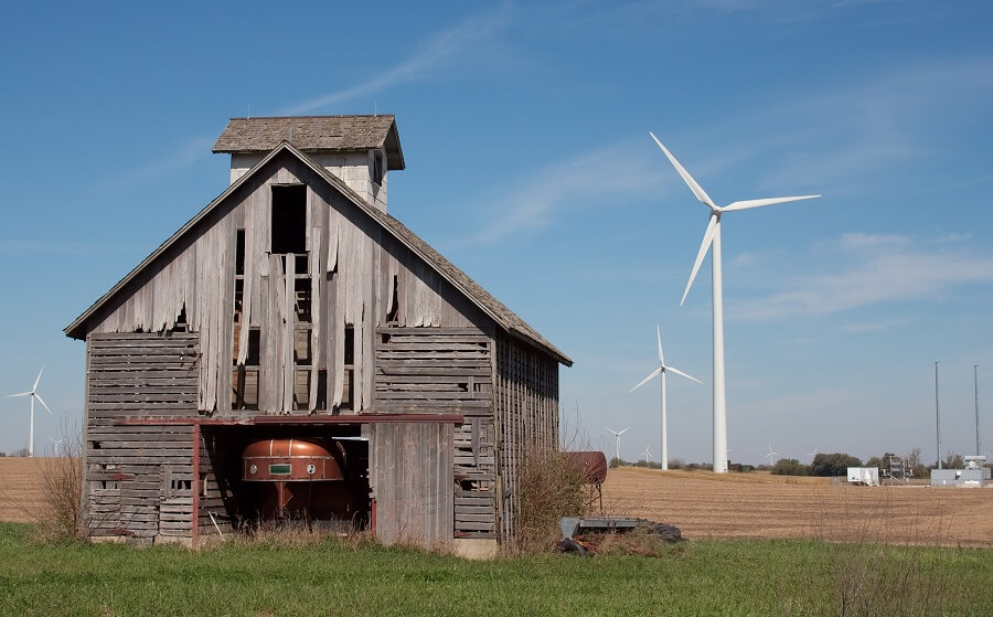 abandoned barn with wind turbines in background