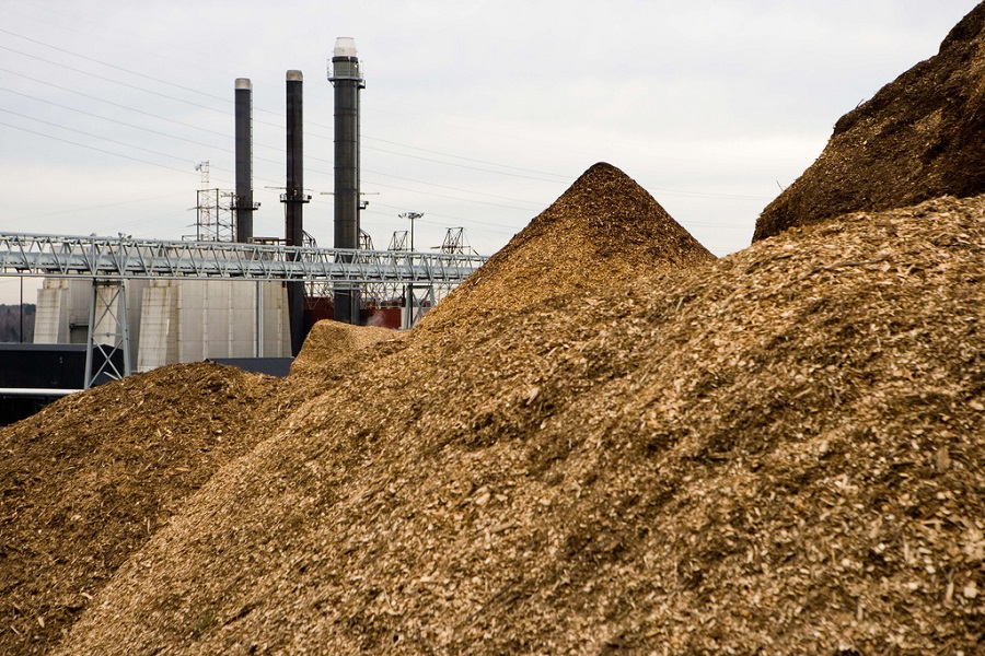 pile of woodchips next to a factory